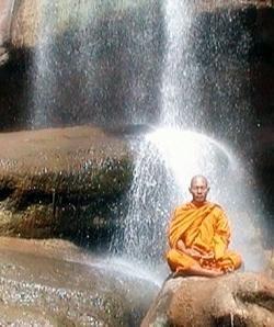 Abbot meditating under waterfall